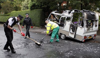 Merseyside police officers help clean up a burned-out camper in the Toxteth area of Liverpool, England, on Wednesday, Aug. 10, 2011, following rioting in the area Tuesday night. (AP Photo/Peter Byrne/PA)