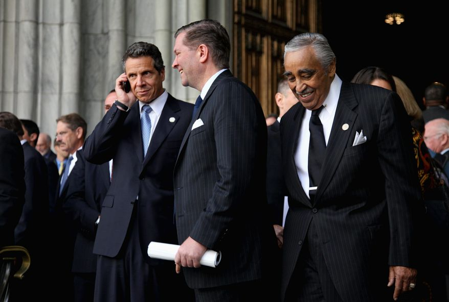 New York Gov. Andrew Cuomo (left, on the phone) and Rep. Charles B. Rangel (far right) leave St. Patrick's Cathedral in New York City on Thursday after the funeral of former New York Gov. Hugh Carey.