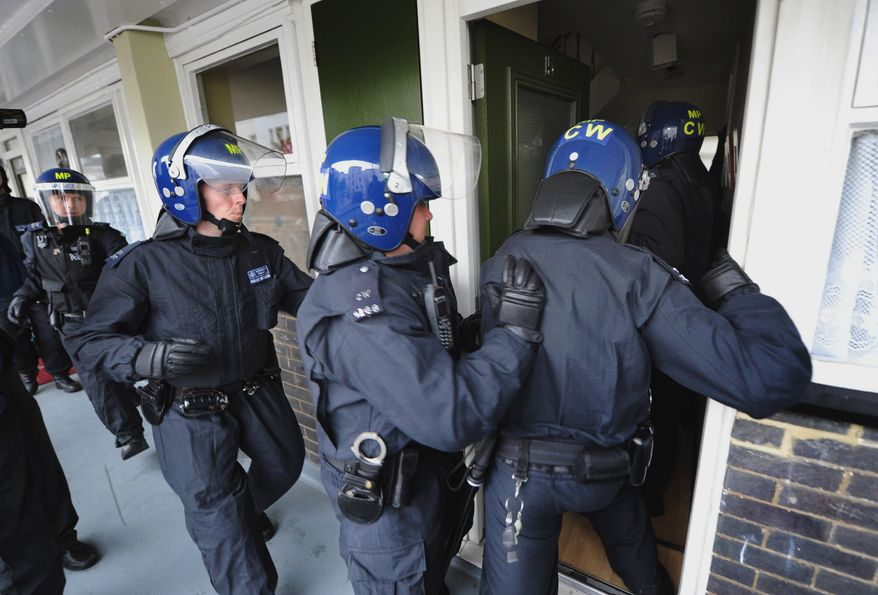 Metropolitan Police officers prepare on Thursday, Aug. 11, 2011, to carry out a raid on a property on the Churchill Gardens estate in London's Pimlico neighborhood during an operation in which police hope to recover property stolen during the recent disturbances in the capital. (AP Photo/Anthony Devlin/PA Wire)