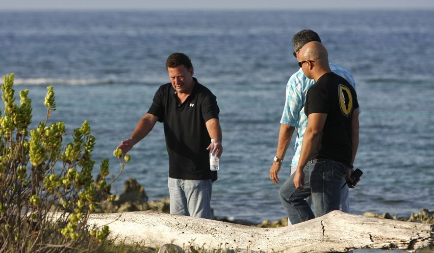 ** FILE ** Gary V. Giordano (left) speaks with Aruban police detectives as they search for his travel partner, Robyn Gardner, 35, of Frederick, Md., at Baby Beach on the southern tip of the Caribbean island on Wednesday, Aug. 3, 2011. (AP Photo/Elton Malone)