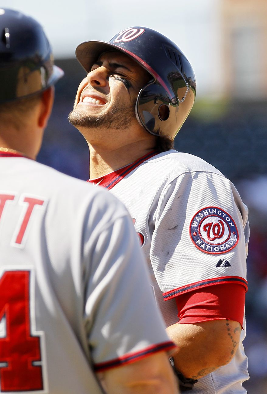 Washington Nationals' Michael Morse grimaces after being hit in the left elbow by a Ryan Dempster fastball in the seventh inning of the Nats' 4-3 loss to the Chicago Cubs. (AP Photo/Charles Rex Arbogast)
