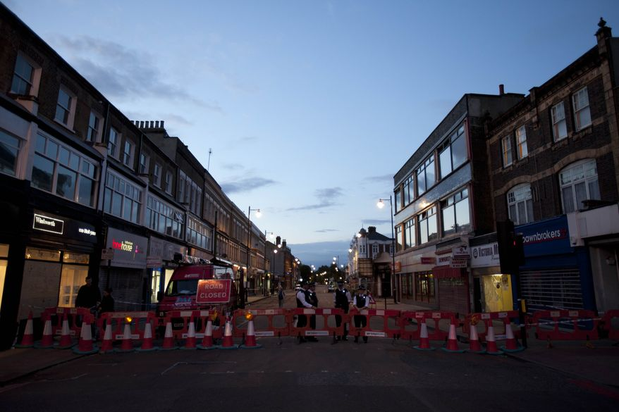 Police stand guard Aug. 11, 2011, as they block access to the high street in Tottenham, north London. (Associated Press)