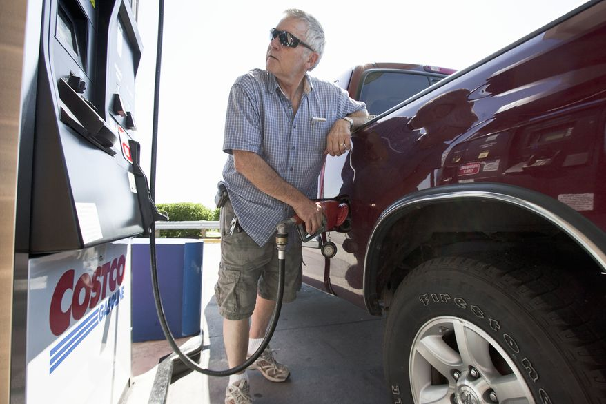 In this photo from Aug. 9, 2011, Gary Hartwig of Gretna, Neb., fuels his car at a Costco gas station in Omaha, Neb. (Associated Press)