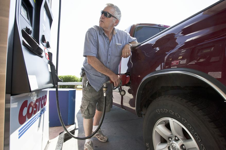 In this Aug. 9, 2011, photo, Gary Hartwig of Gretna, Neb., fuels his car at a Costco gas station in Omaha, Neb. Consumers spent more on autos, furniture and gasoline in July, pushing up retail sales by the largest amount in four months. The gain could signal that Americans are a little more confident and help dispell fears that the country is in danger of toppling into another recession. (AP Photo/Nati Harnik)