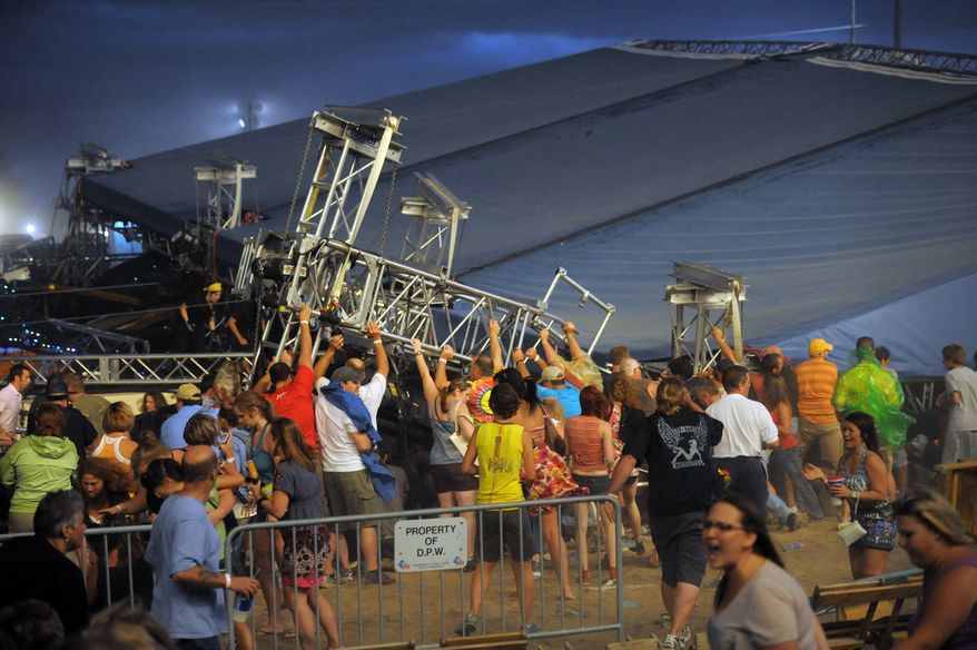 ** FILE ** Fans waiting to see the duo Sugarland attempt to hold up the stage after high winds blew it over at the Indiana State Fair on Saturday, Aug. 13, 2011, in Indianapolis. (AP Photo/The Indianapolis Star, Matt Kryger, File)
