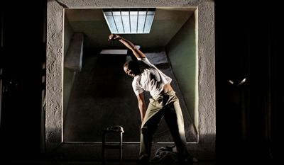 """ASSOCIATED PRESS Aubrey Lodewyk portrays Nelson Mandela exercising in his Robben Island prison cell during a dress rehearsal for the new opera """"Mandela Trilogy,"""" which opened in Johannesburg on Saturday. """"Trilogy"""" traces Mr. Mandela's life from boyhood to his rise as a political leader, imprisonment and eventual release."""