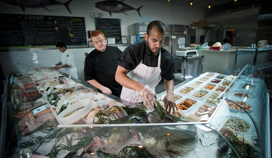 GOING GOURMET: Executive chef Richard Cook (above left) and market manager Sergio Rarujo arrange the main display case at BlackSalt in the Palisades, one of many new restaurants that have enlivened the D.C. dining scene. (Andrew S. Geraci/The Washington Times)
