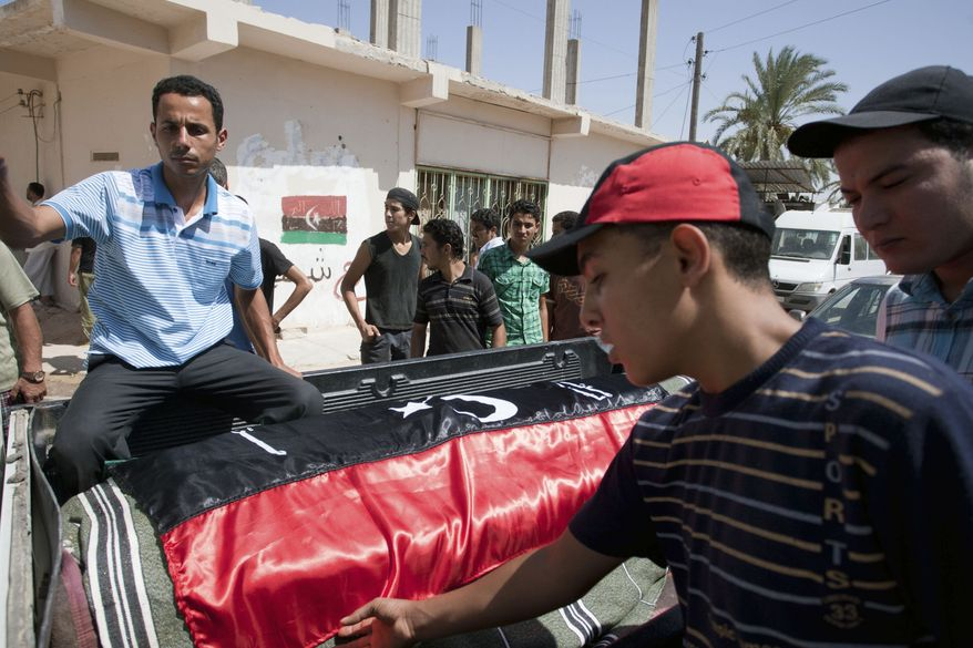 A Libyan rebels carry the coffin of a comrade in Zawiya, western Libya, Libya, Monday, Aug. 15, 2011. Libya's rebels threatened to isolate Tripoli by blocking key supply routes and cutting oil pipelines on Monday after a dramatic weekend advance put them in the strongest position since the 6-month-old civil war began to attack Moammar Gadhafi's stronghold. (AP Photo/Giulio Petrocco)