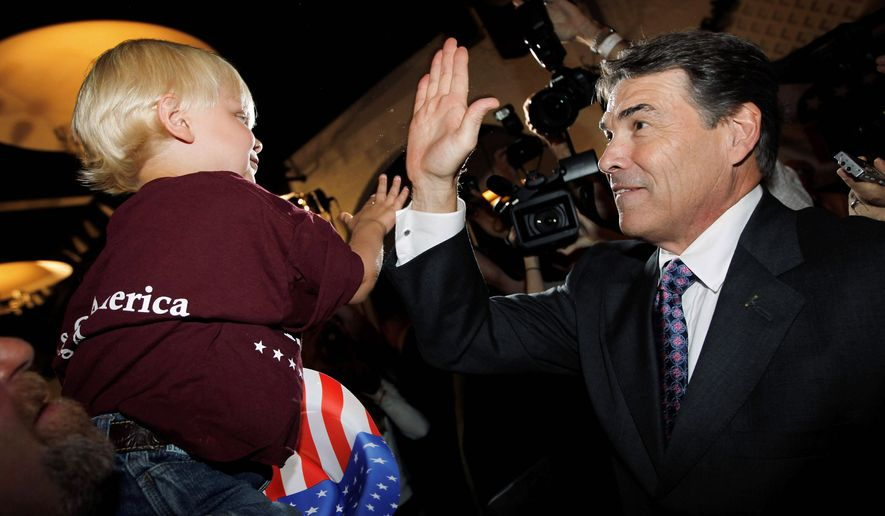 MAKING FRIENDS: Texas Gov. Rick Perry, the newest Republican presidential candidate, high-fives Remington Tack, 4, at the Black Hawk County Republican Party Lincoln Day Dinner in Waterloo, Iowa, on Sunday. (Associated Press)