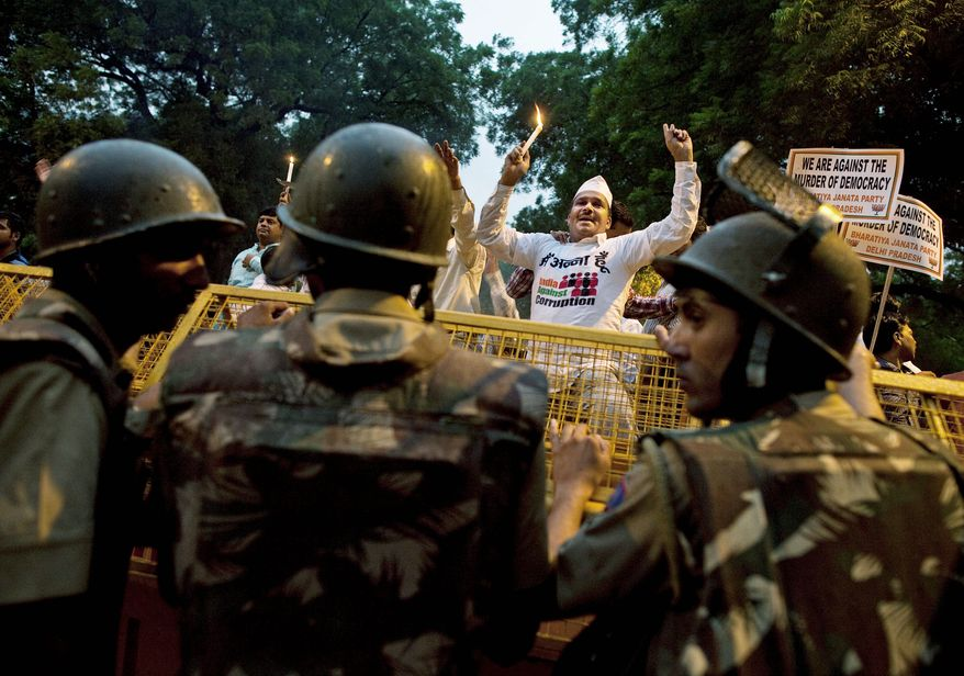 ASSOCIATED PRESS PHOTOGRAPHS A supporter of Indian anti-corruption activist Anna Hazare shouts slogans while holding a candle in New Delhi on Tuesday. Mr. Hazare began fasting behind bars as his supporters held protests across the country, with thousands detained by police.