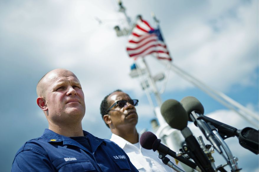 Coast Guard Lt. Cmdr. Randall Brown (left) and D.C. Fire Chief Kenneth Ellerbe discuss a black sheen seen on the Anacostia River Monday and Tuesday. First water samples tested positive for petroleum. (Drew Angerer/The Washington Times)