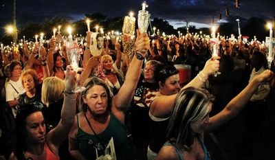 Fans of Elvis Presley from all over the world gather at the gates of his Graceland mansion for a candlelight vigil on Monday, Aug. 15, 2011, in Memphis, Tenn., to mark the 34th anniversary of his death. (AP Photo/Memphis Commercial Appeal, Jim Weber)