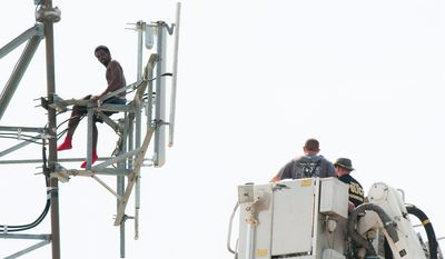 Negotiators in a ladder truck attempt to persuade a man on the Clear Channel Communications broadcast tower to come down on Aug. 15, 2011, the fifth day of a standoff with police after the man climbed the tower. (Associated Press/Tulsa World)