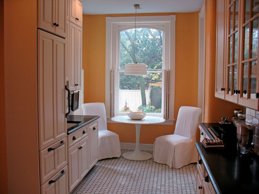 The kitchen has a marble floor, black granite counters and white cabinets.