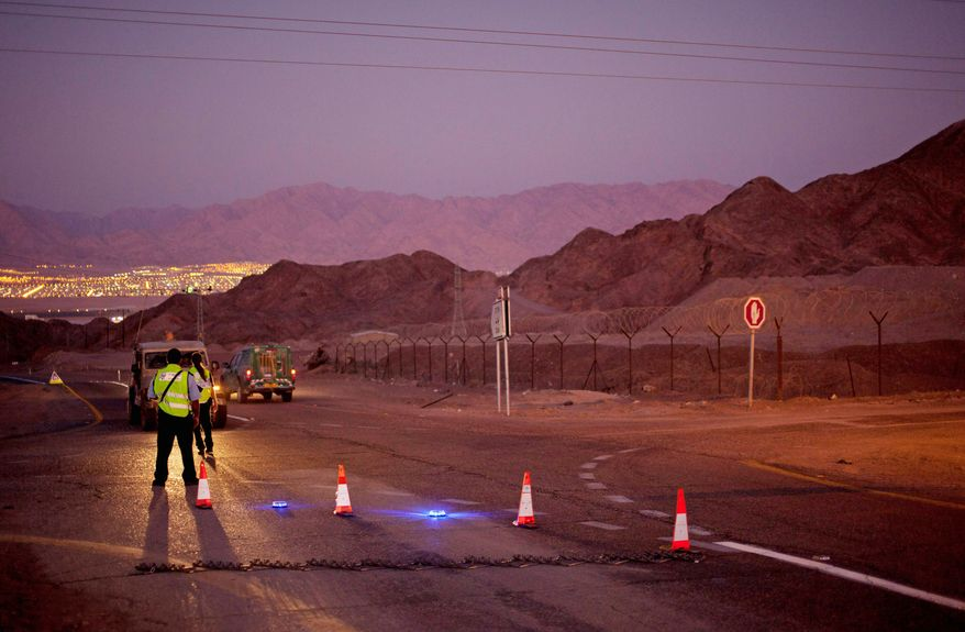 Police officers stop the traffic on a road in the Arava Desert leading to the southern Israeli town of Eilat on Thursday after gunmen crossed from the neighboring Egyptian Sinai Peninsula. They killed six Israelis and wounded at least a dozen in a string of attacks. (Associated Press)