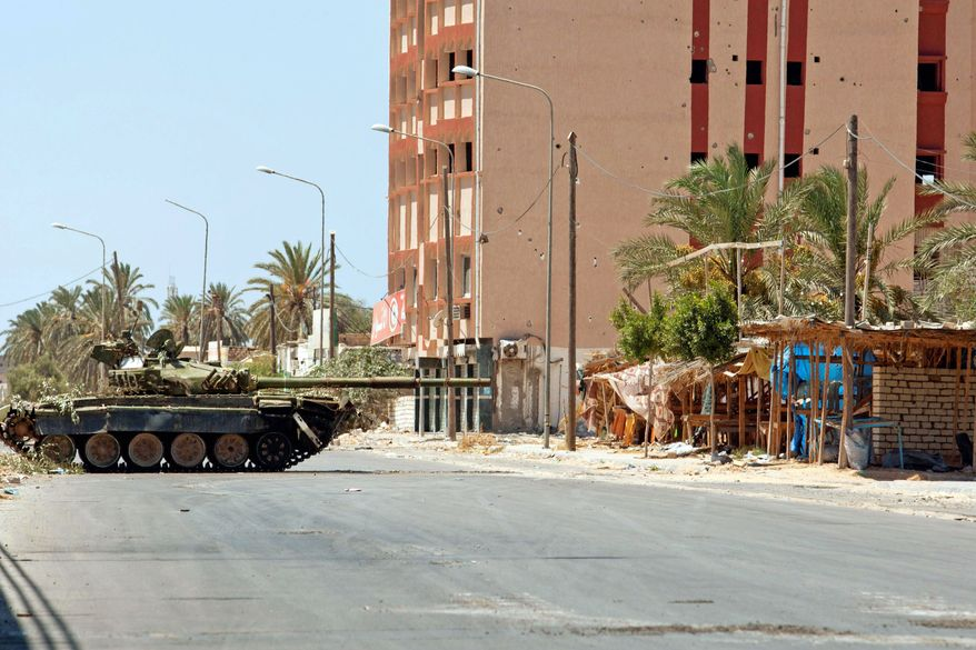 A Libyan rebel tank that once belonged to troops loyal to Col. Moammar Gadhafi blocks access to a road in Zawiya on Sunday. (Associated Press)