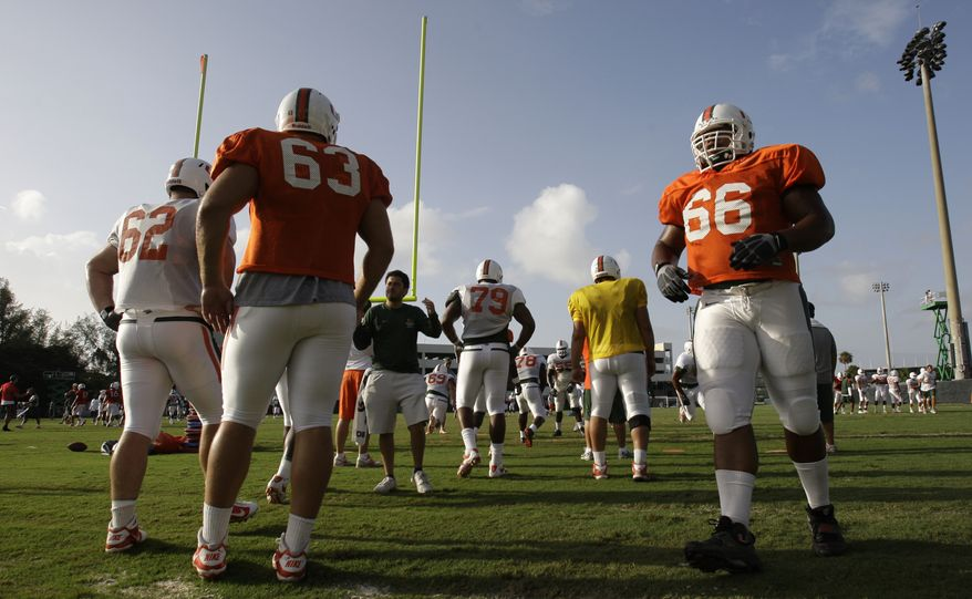 "Miami offensive lineman Harland Gunn (66) does running drills during football practice in Coral Gables, Fla., Thursday, Aug. 18, 2011. Miami's head coach Al Golden says his team is recovering from the shock of scandalous allegations hitting the program and sparking talk from the NCAA for ""fundamental change"" in college sports. Also shown are offensive linemen Shane McDermott (62) and Tyler Horn (63). (AP Photo/Lynne Sladky)"