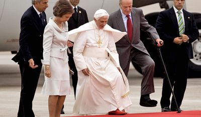 Pope Benedict XVI mounts the saluting stand next to King Juan Carlos, right, and Queen Sofia of Spain Juan Carlos as he arrives at Barajas Airport in Madrid, Spain, Thursday Aug. 18, 2011. (AP Photo/Emilio Morenatti)