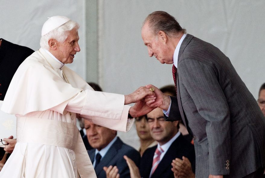 King Juan Carlos bows in front of Pope Benedict XVI he arrives at the airport in Madrid, Spain, Thursday Aug. 18, 2011. (AP Photo/Emilio Morenatti)