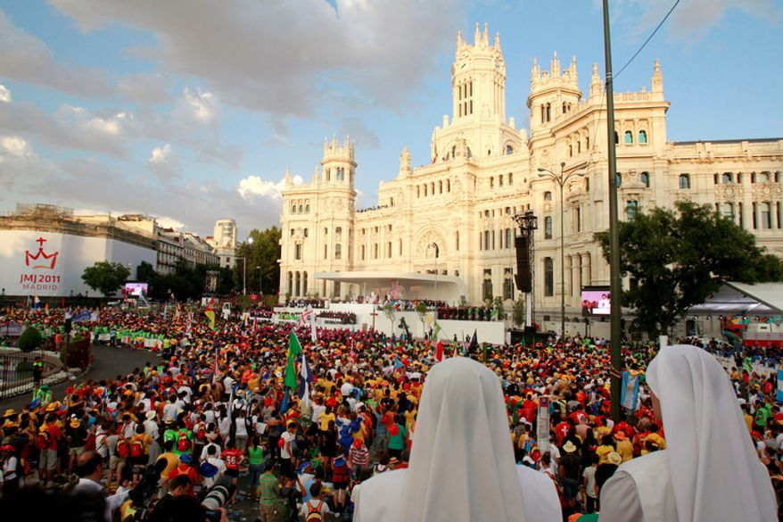Worshippers join Pope Benedict XVI, on the stage at center, in a prayer at Madrid's Cibeles square Thursday Aug. 18, 2011. The Pope arrived Thursday for a four-day visit to celebrate World Youth Day. (AP Photo/Armando Franca)