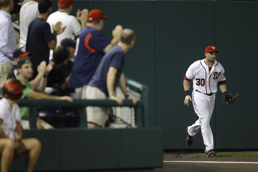 Washington Nationals left fielder Jonny Gomes is applauded by fans after making a running catch on a flyball by Cincinnati Reds' Joey Votto to end the fifth inning on Thursday. Gomes also had a two-run single in the Nationals' 3-1 win. (AP Photo/Jacquelyn Martin)
