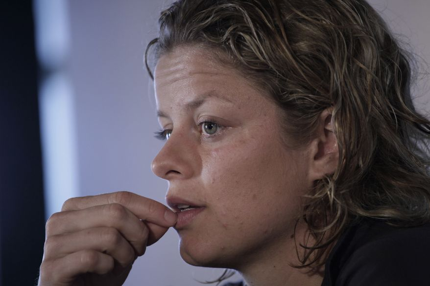 FILE - This June 14, 2011, file photo shows Kim Clijsters of Belgium answering questions during a news conference after losing her match against Romina Oprandi of Italy at the women's singles Unicef Open tennis tournament in Rosmalen, central Netherlands. The two-time defending U.S. Open champion will not go for three in a row this year because of a stomach muscle injury. (AP Photo/Peter Dejong, File)
