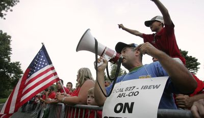 Art Plotka (holding bullhorn), of Windsor, N.J., and other striking Verizon workers protest during a candlelight vigil at the home of Verizon CEO Lowell McAdam in Mendham, N.J., on Aug. 18, 2011. (Associated Press)