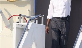 President Obama waves as he exits Air Force One at the Cape Cod Coast Guard Station in Bourne, Mass., on Thursday, Aug. 18, 2011, on his way to Martha's Vineyard. (AP Photo/Stew Milne)