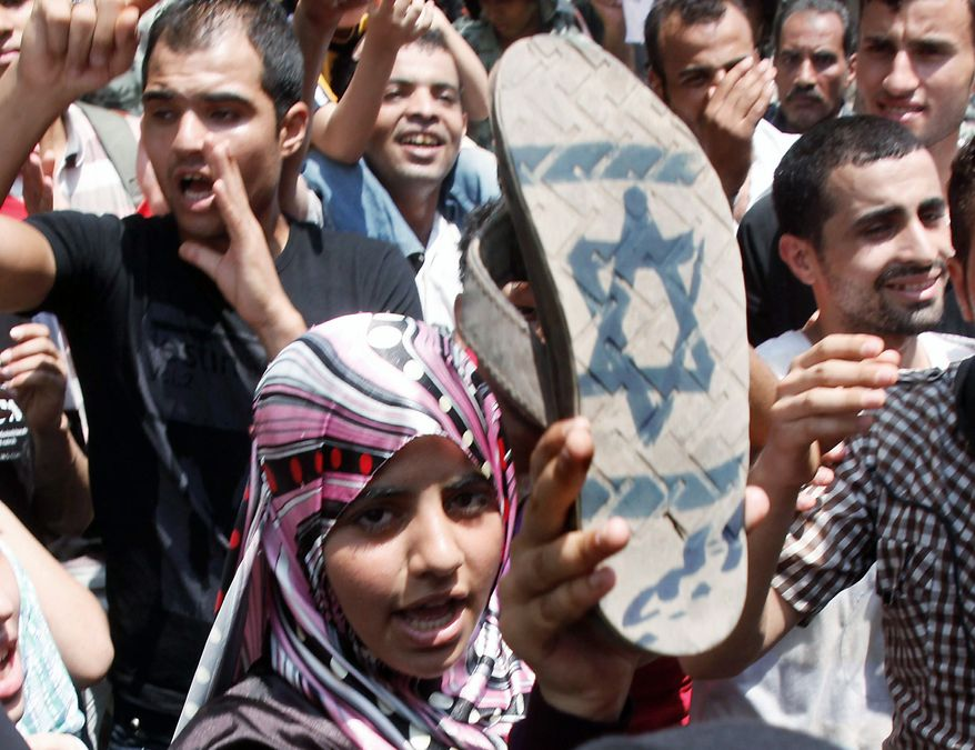 ASSOCIATED PRESS An Egyptian girl displays a sole of her shoe painted with an Israeli flag during a protest Sunday in front of the Israeli Embassy in Cairo. Hundreds of Egyptians protested the deaths of Egyptian security forces killed in a shootout between Israeli soldiers and Palestinian militants on Thursday in the Sinai.