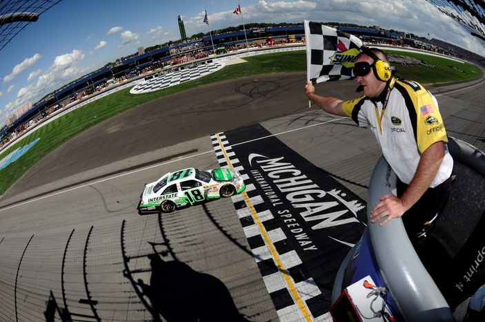 ASSOCIATED PRESS Kyle Busch crosses the finish line at Michigan International Speedway for the Sprint Cup points leader's fourth season victory .