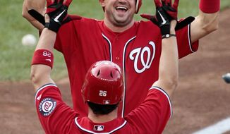 Nationals third baseman Ryan Zimmerman is all smiles as he's greeted at home by Jesus Flores in the 10th inning. Zimmerman doubled to start the winning rally.