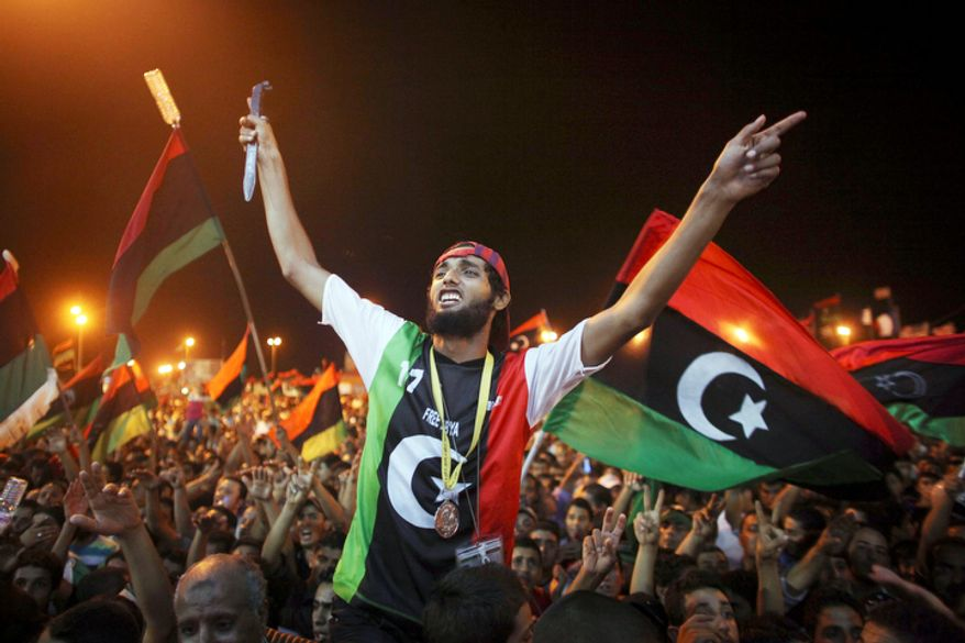 People celebrate the capture in Tripoli of Moammar Gadhafi's son and one-time heir apparent, Seif al-Islam, at the rebel-held town of Benghazi, Libya, early Monday, Aug. 22, 2011.  (AP Photo/Alexandre Meneghini)