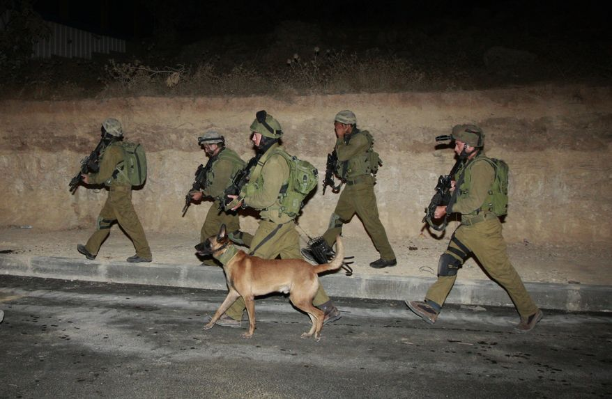 Israeli soldiers patrol during a military operation in the West Bank city of Hebron early on Sunday, Aug. 21, 2011. Israeli troops rounded up 50 Hamas activists in the West Bank in an overnight raid, Palestinian security officials said. (AP Photo/Nasser Shiyoukhi)