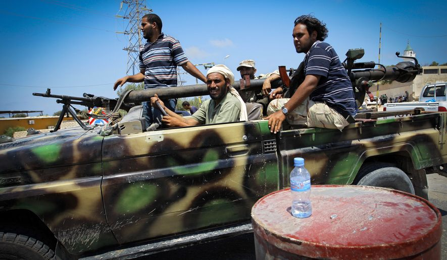 Libyan rebel fighters speed toward the front-line fighting in the village of Mayah, Libya, some 18 miles west of Tripoli, the capital, on Sunday, Aug. 21, 2011. (AP Photo/Sergey Ponomarev)