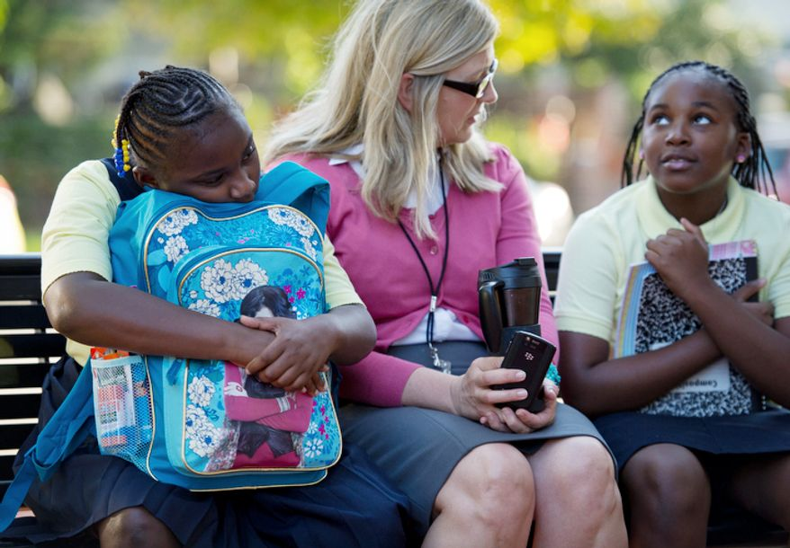 John Tyler Elementary School Principal Jennifer Frentress (center) chats with students Tatyanna Liggins, 9, (left) and Ty-Tiana Corbin, 9, (right) during the arrival of students and their parents for the first day of school at John Tyler Elementary School in Washington, DC, Monday, August 22, 2011. (Rod Lamkey Jr./The Washington Times)