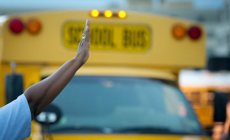 A crossing guard directs school buses on the first day of school year. (Rod Lamkey Jr./The Washington Times)