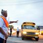 Ivory Darell directs school buses on the first day of school in Washington, DC. (Rod Lamkey Jr./The Washington Times) **FILE**