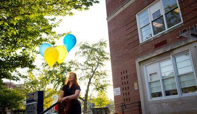 John Tyler Elementary School Arts Integration Coordinator Lauren Eskovitz arranges balloons out front in preparation for the arrival of students for the first day of school at John Tyler Elementary School. (Rod Lamkey Jr./The Washington Times)