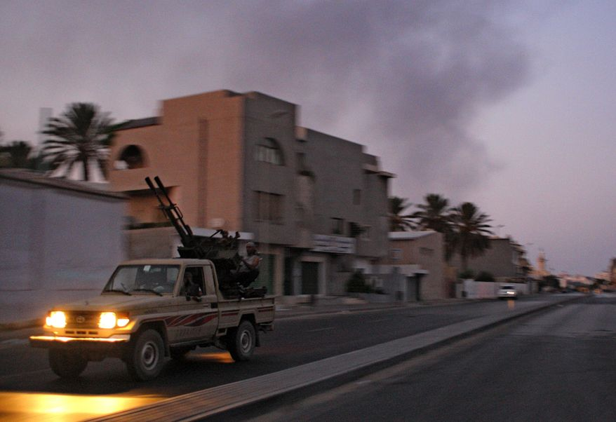 An armored vehicle speeds on the outskirts of Tripoli as huge smoke rises over the downtown area on Aug. 22, 2011. (Associated Press)