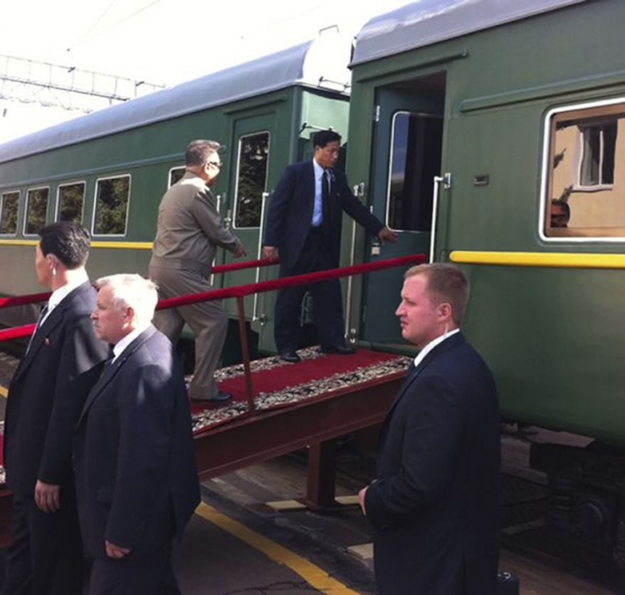 North Korean leader Kim Jong-il (in tan suit) walks up a ramp to the carriage of his armored train at the Bureya railway station in Russia's eastern Siberia region on Sunday, Aug. 21, 2011. (AP Photo/IA Port Amur, www.portamur.ru)
