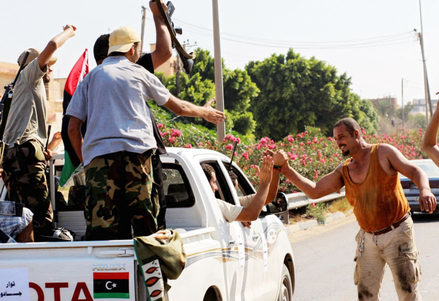 Local residents greet advancing rebel fighters on the outskirts of Tripoli, Libya, Monday, Aug. 22, 2011. Clashes broke out early Monday near Moammar Gadhafi's compound in Tripoli, a day after rebels poured into the Libyan capital. (AP Photo/Sergey Ponomarev)