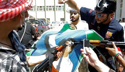 Libyan rebel fighters from Tripoli brigade deface a portrait of Libyan dictator Moammar Gadhafi in Tripoli, Libya.  (AP Photo/Sergey Ponomarev)