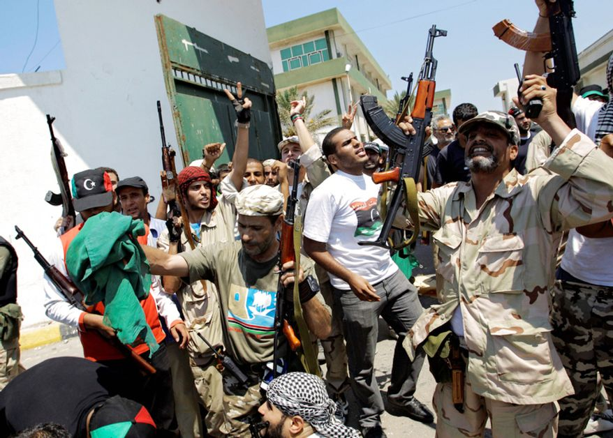 Libyan rebel fighters gesture at the former military base in Tripoli, LIbya, Monday, Aug. 22, 2011. Libyan rebels claimed to be in control of most of the Libyan capital on Monday.  (AP Photo/Sergey Ponomarev)