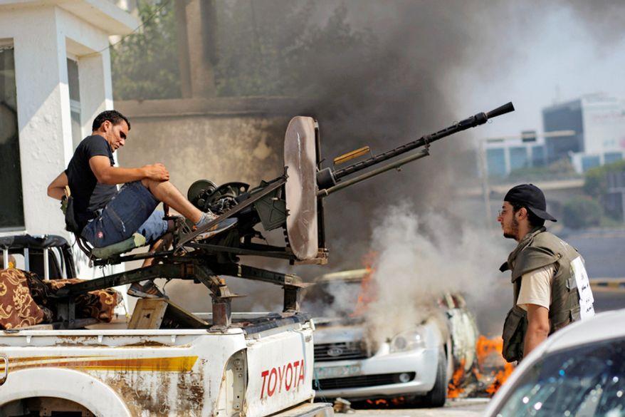 Libyan rebel fighters prepare to shoot towards pro-Gadhafi forces during fighting in downtown Tripoli, LIbya. (AP Photo/Sergey Ponomarev)
