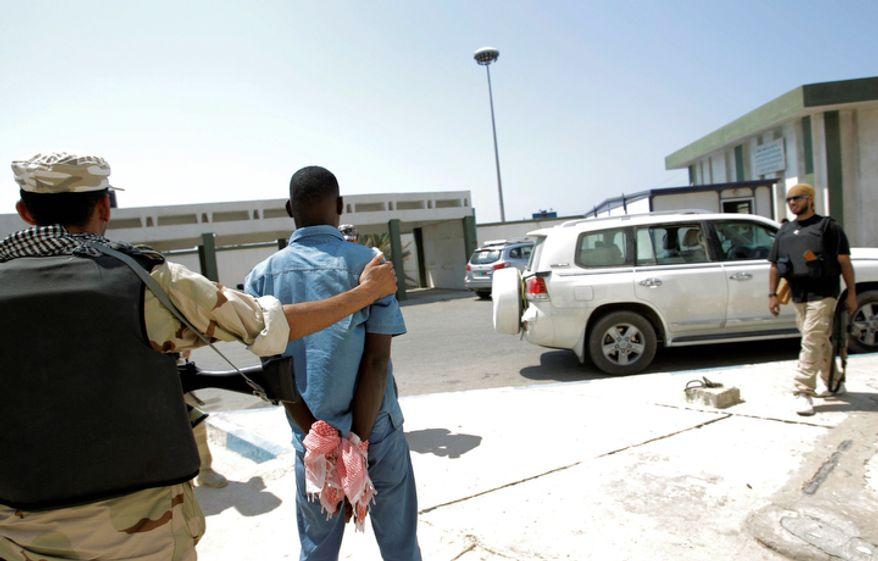 A Libyan rebel fighter holds a captured pro-Gadhafi fighter, center, inside a military base in Tripoli, Libya. (AP Photo/Sergey Ponomarev)