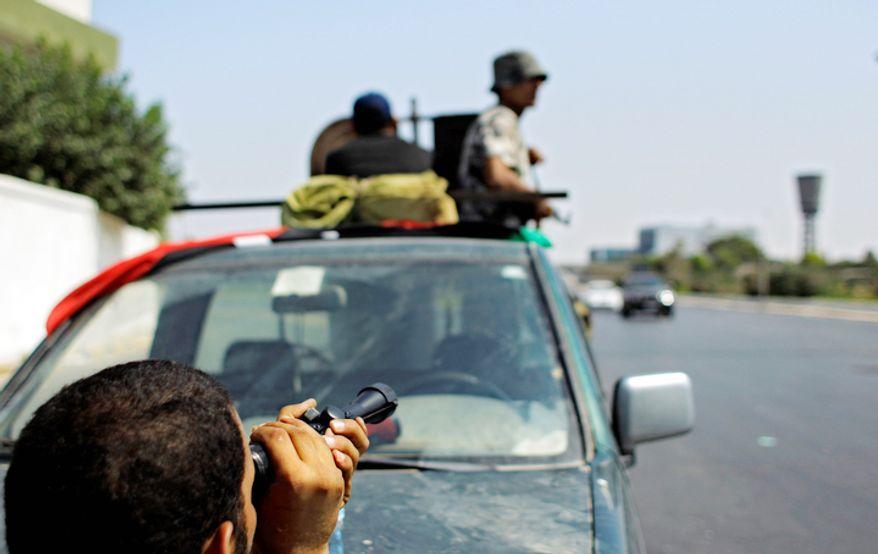 A Libyan rebel fighter looks through a scope  in Tripoli, LIbya. (AP Photo/Sergey Ponomarev)