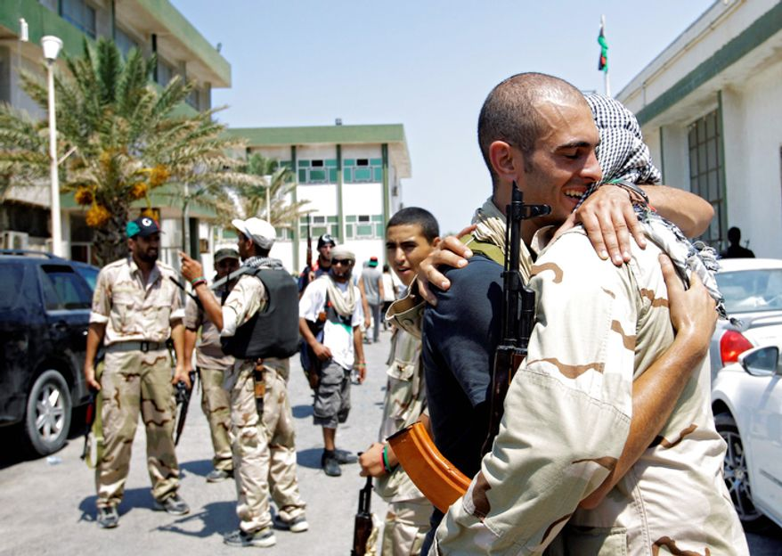 Libyan rebel fighters embrace at a military base in Tripoli, Libya, Monday, Aug. 22, 2011. Libyan rebels claimed to be in control of most of the Libyan capital on Monday after their lightning advance on Tripoli heralded the fall of Moammar Gadhafi's nearly 42-year regime, but scattered battles erupted and the mercurial leader's whereabouts remained unknown. (AP Photo/Sergey Ponomarev)