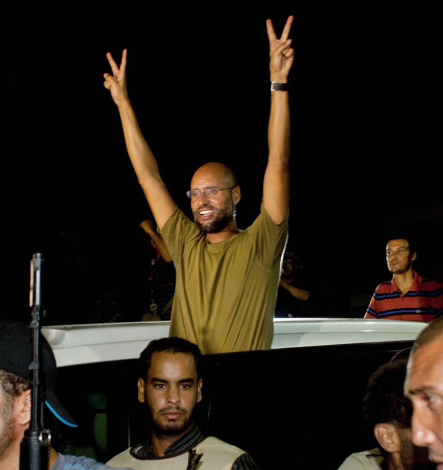 Moammar Gadhafi's son, Seif al-Islam waves to troops loyal to his father in Tripoli, Libya, early Tuesday, Aug. 23, 2011. Al-Islam, who had been reported arrested by Libya's rebels, turned up Tuesday morning at the hotel where foreign journalists stay in Tripoli, then took reporters in his convoy on a drive through the city. (AP Photo/Dario Lopez-Mills)
