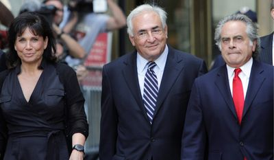 ASSOCIATED PRESS Former International Monetary Fund leader Dominique Strauss-Kahn (center) leaves Manhattan state Supreme Court with his wife, Anne Sinclair, and attorney Benjamin Brafman after a hearing Tuesday in New York. A New York judge dismissed the sexual assault case against Mr. Strauss-Kahn.