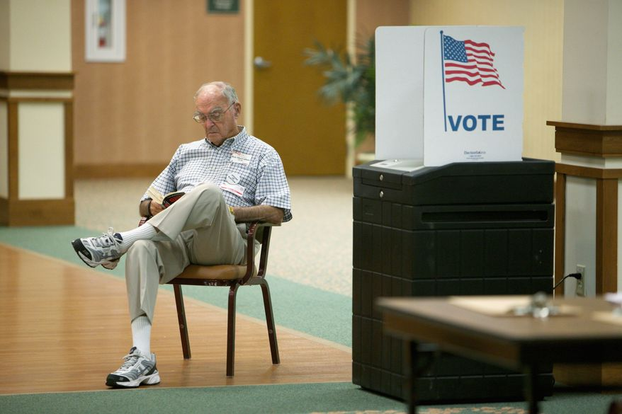 Election official Bob MacCallum reads a book while awaiting voters at the Greenspring retirement community in Springfield on Tuesday. (Andrew Harnik/The Washington Times)